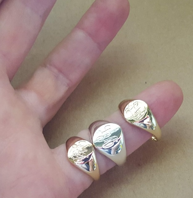 gold and silver signet rings on fingers